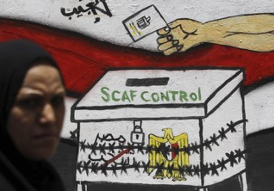 Egyptian walks past 'SCAF Control' graffiti