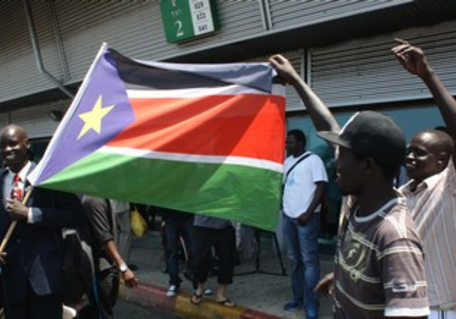 Migrants dance with South Sudanese flag
