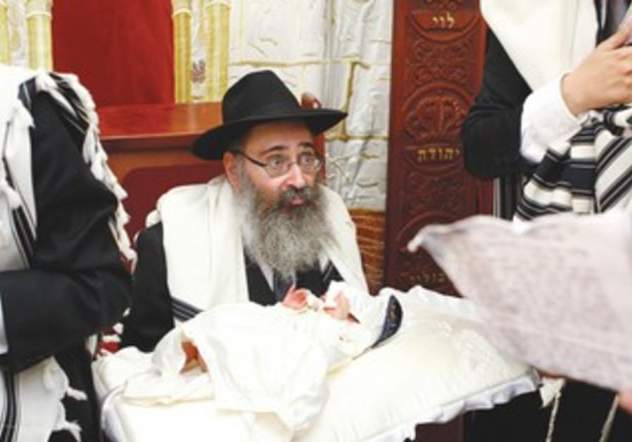 Rabbi holds boy for circumcision
