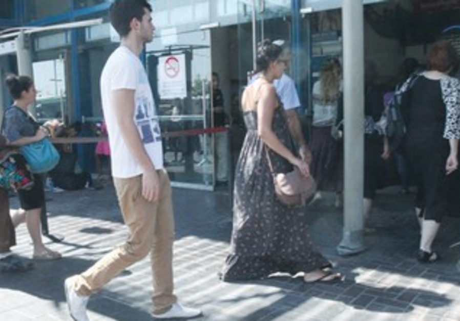 People walk through metal detectors at bus station