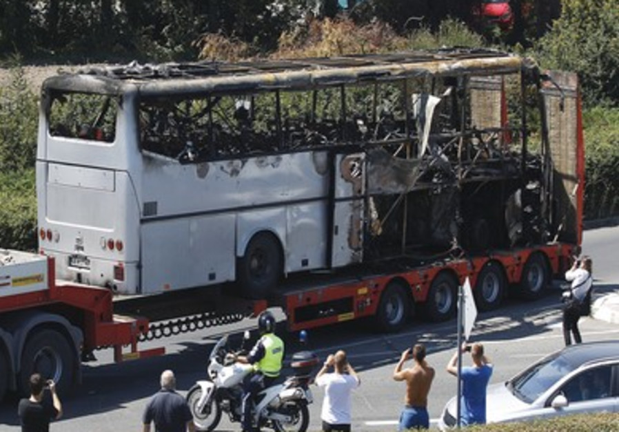 Truck carries bus damaged in terrorist attack