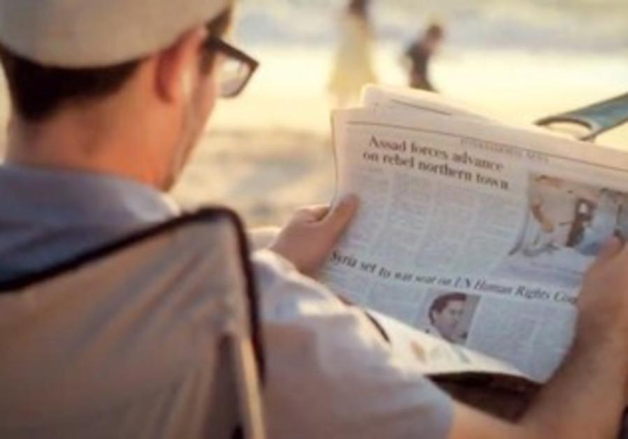 MAN reads a copy of 'The Jerusalem Post'