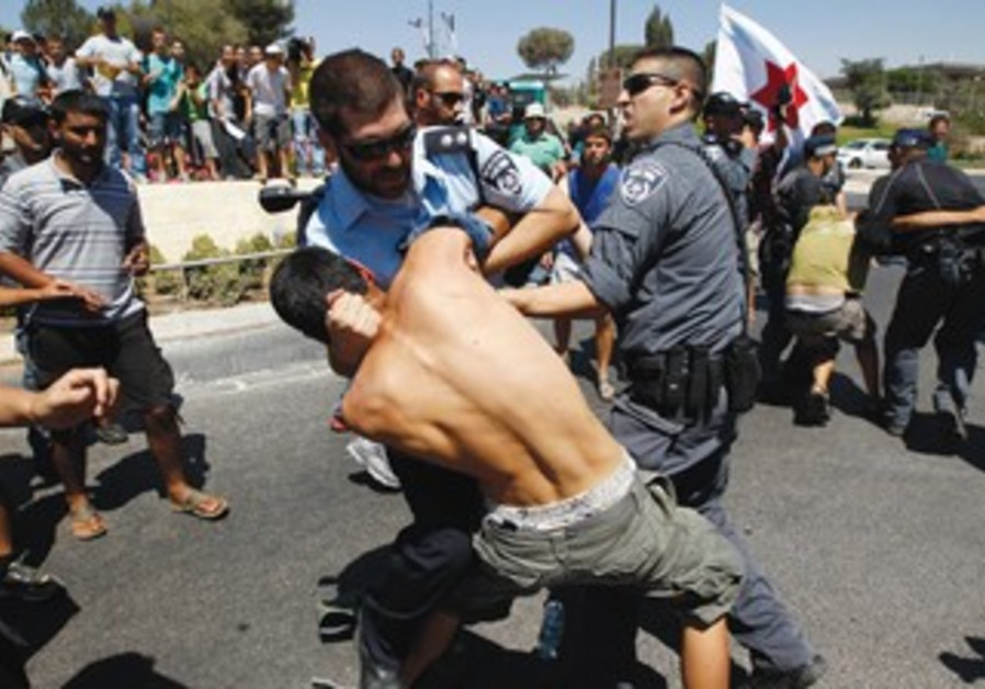 POLICE DETAIN youths taking part in a protest