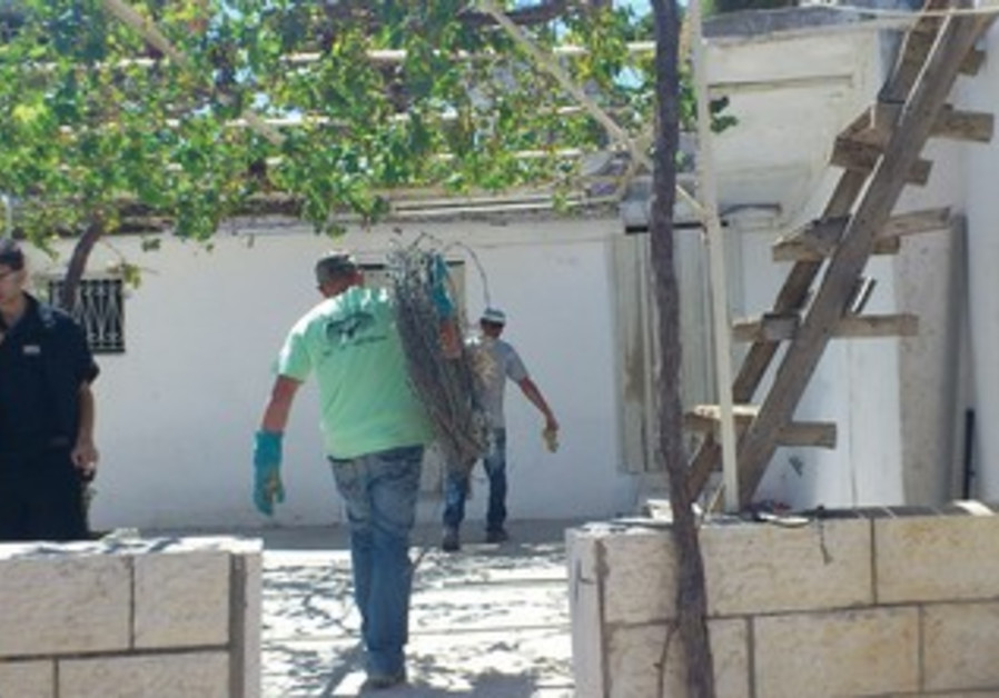 Activist with barbed wire to block e. j'lem home