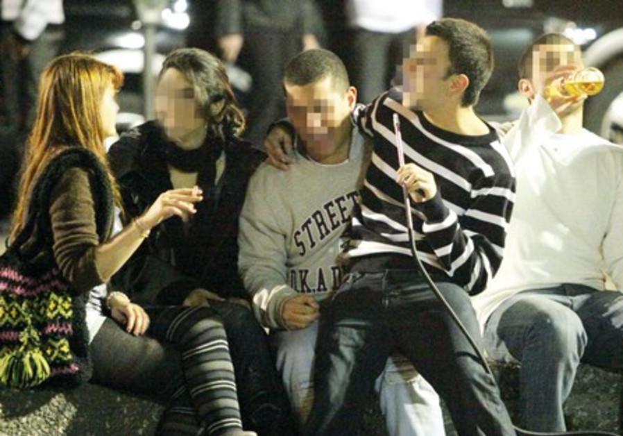Teenagers drinking and smoking Hookah