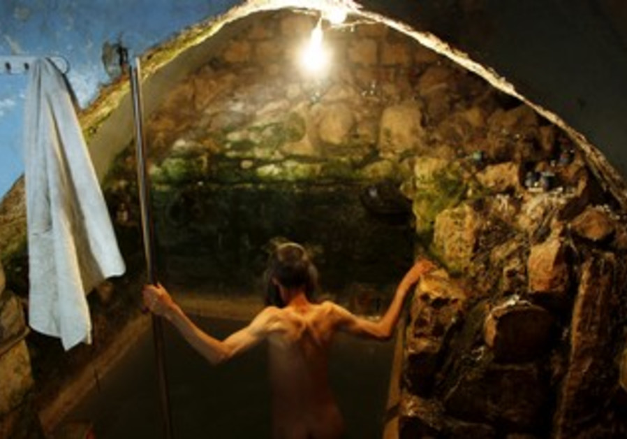 An Orthodox Jew enters into a ritual bath in Safed