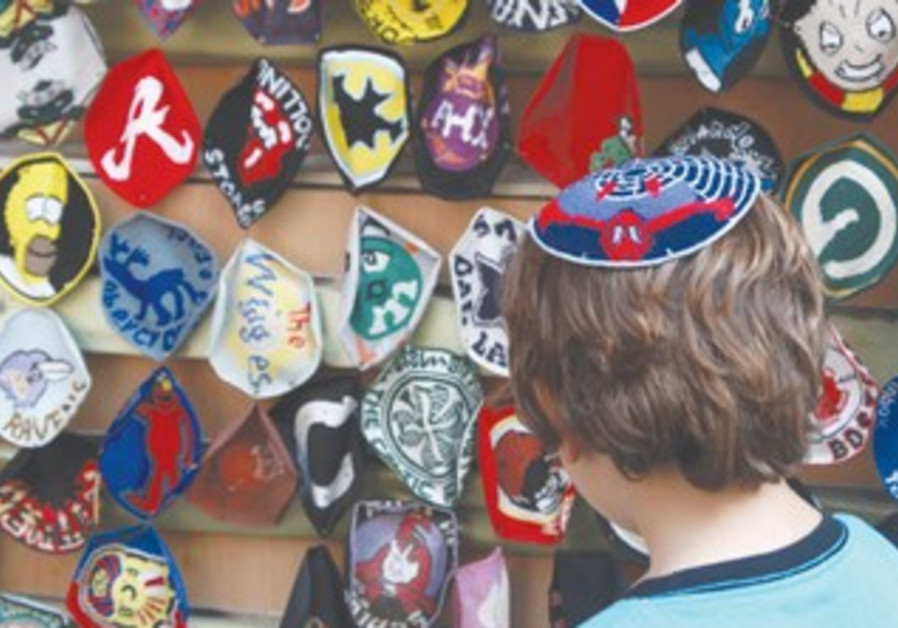 Boy looks at selection of kippot in shop