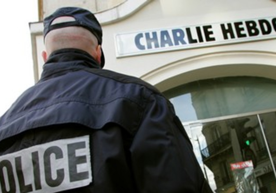 "A policeman stands guard outside ""Charlie Hebdo"""