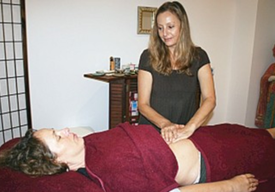 Sidika Ashauer performs acupuncture on a patient