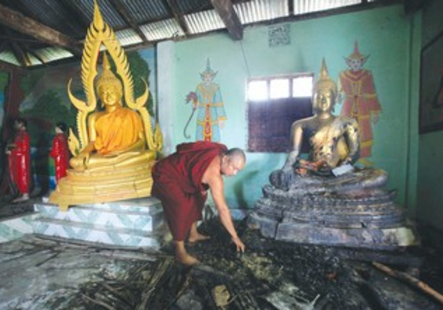 Buddhist monk inspects a burnt temple