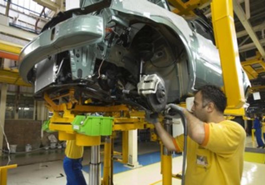 Iranian employees assemble car in Tehran plant