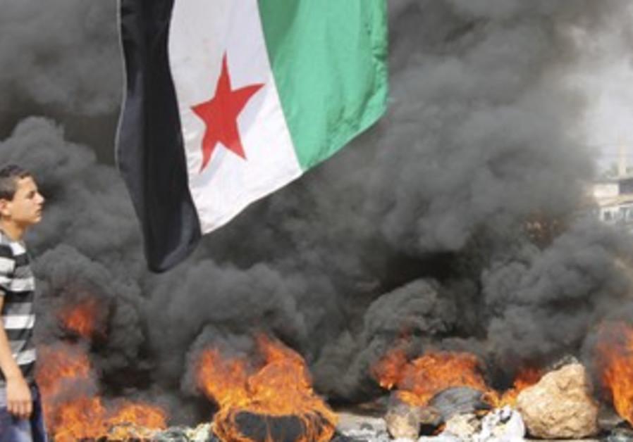 Boy walks past burning tires in Beirut protest