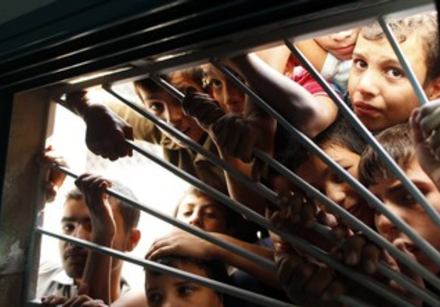 Palestinian boys look through morgue window