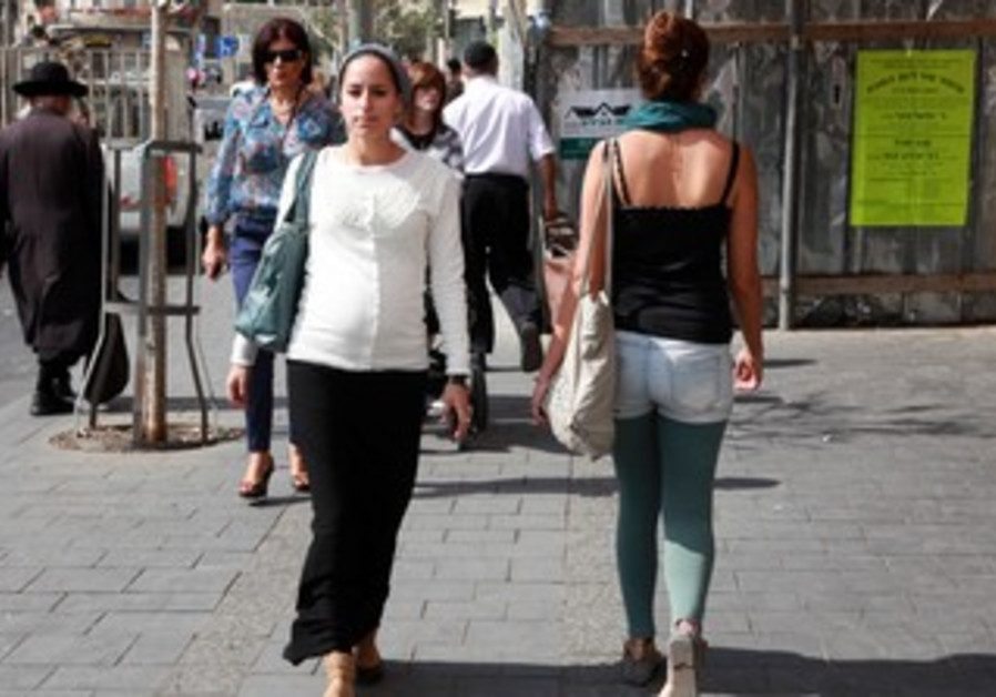 A secular woman walks by a religious woman on the street in Jaffa.
