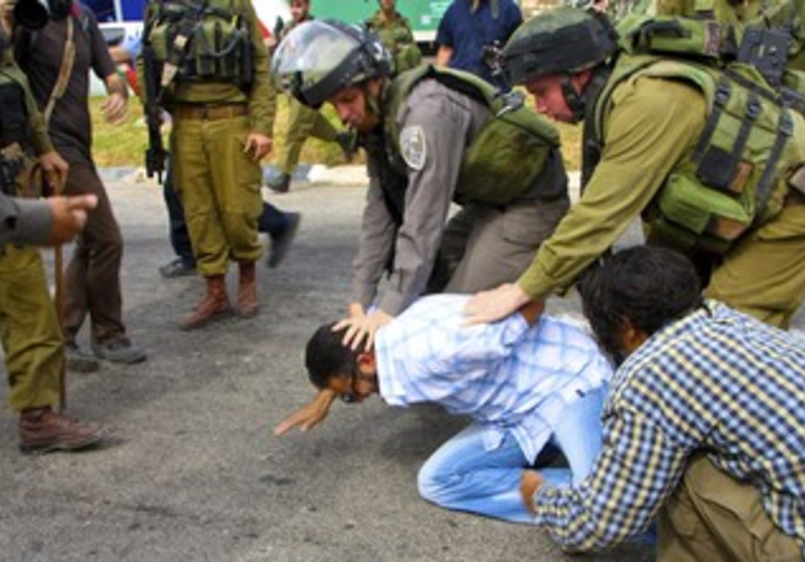 Border police and soldiers restrain a Palestinian