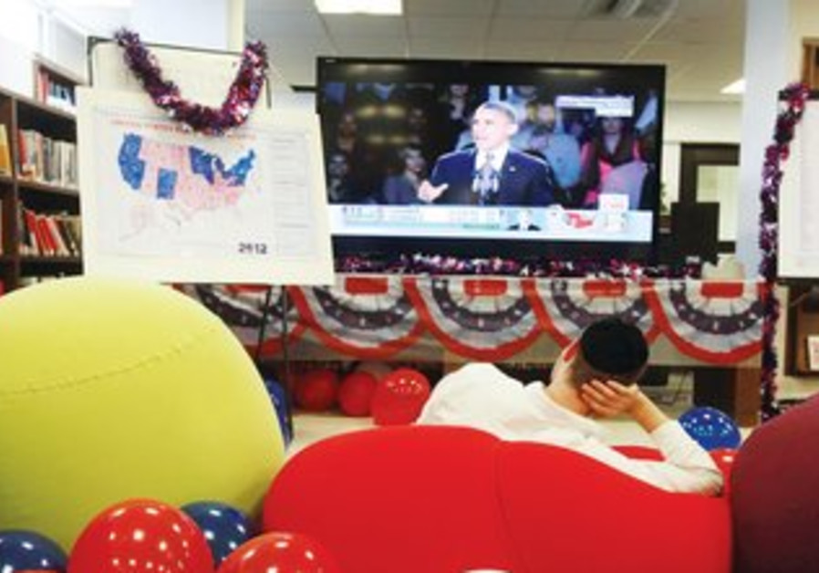 Man watches US election results in party in J'lem.