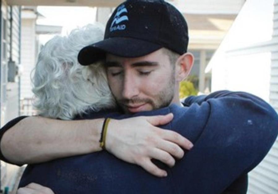 A VOLUNTEER working for IsraAID hugs a resident