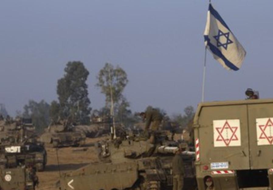 IDF tanks and a flag on the Gaza border