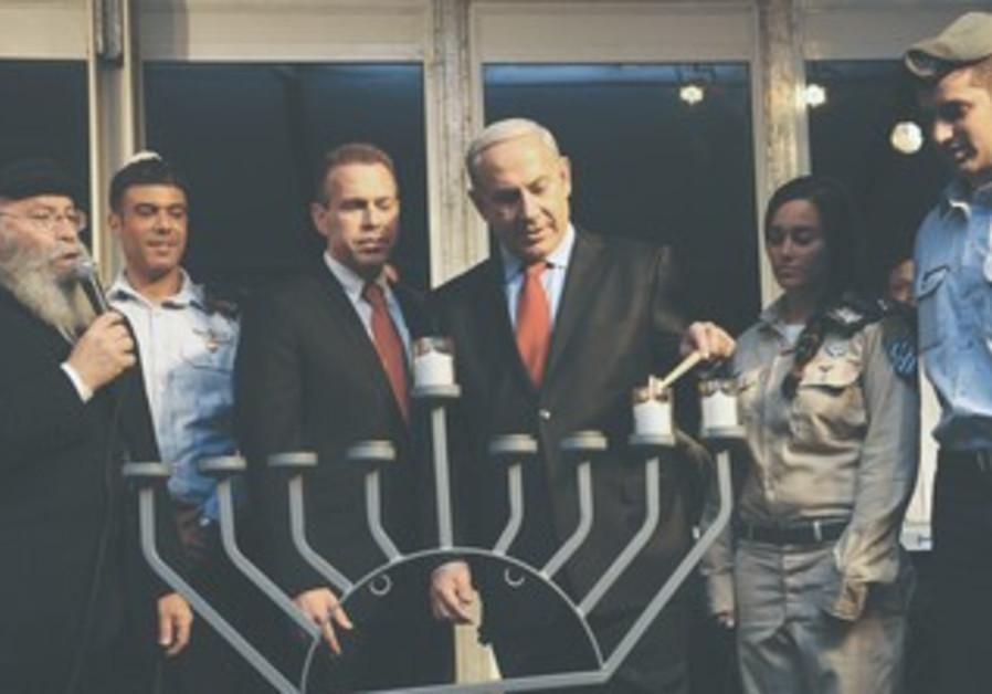 Netanyahu and Erdan light Hannuka candles.