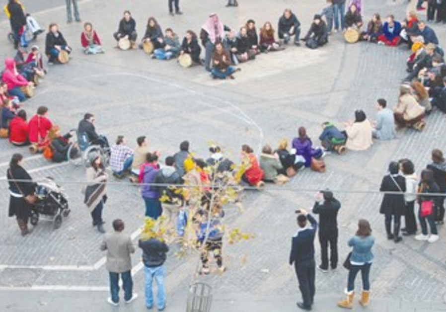 Peace activists in heart-shaped drum circle