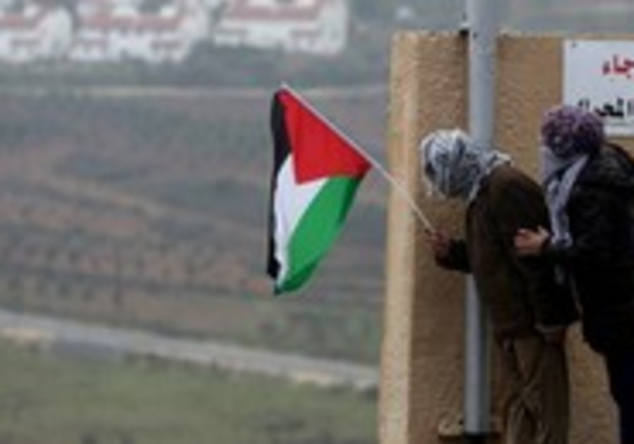 Palestinians hold a flag in the West Bank