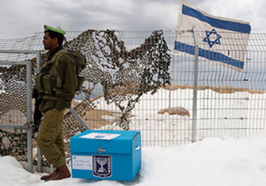 An IDF soldier stands with a ballot box at a base on the Golan Heights, during the 2009 elections