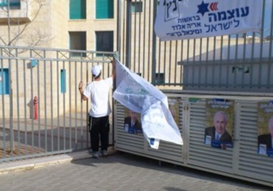Bayit Yehudi activist removes banner after CEC ruling, Jan. 22, 2013