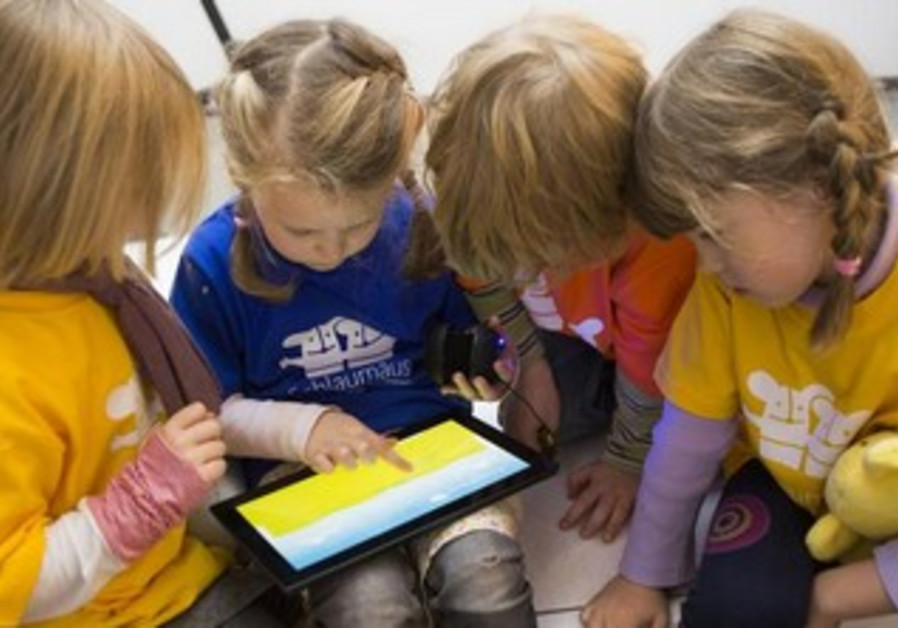 Children play with Microsoft's education software that runs on a Windows 8 operated tablet computer.