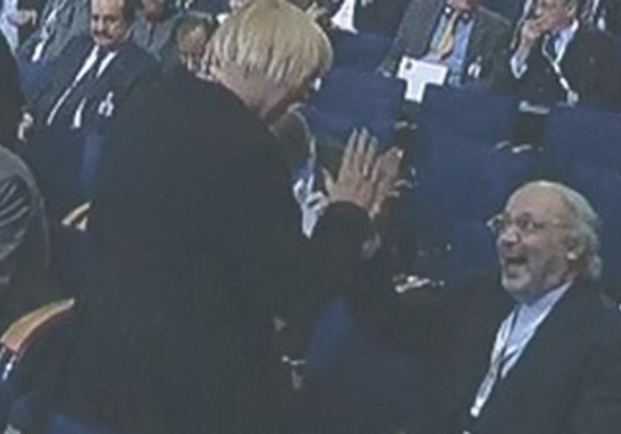 CLAUDIA ROTH, head of Germany's Green Party, high-fives Iranian Ambassador Ali Reza Sheikh Attar