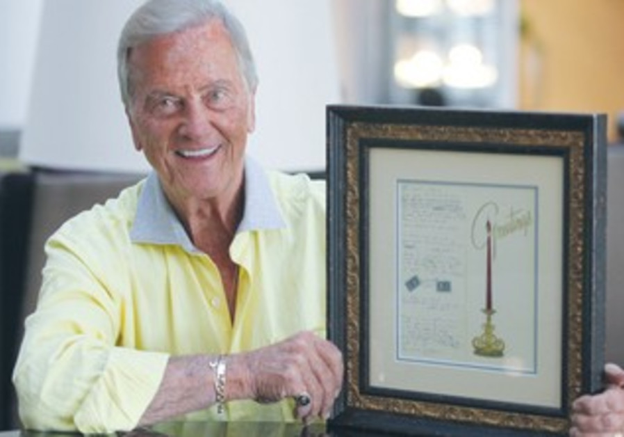 PAT BOONE holds up the framed Christmas card on which he wrote the lyrics to his song.