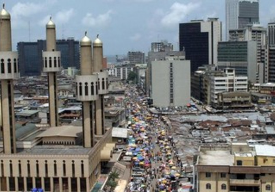 People and traffic move along a busy street in Lagos, Nigeria, May 24,2005.
