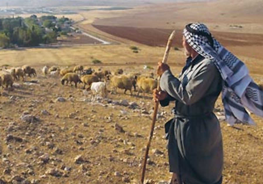 A Beduin man stands on a bluff overlooking the village of Al-Hadidya in the Jordan Valley.