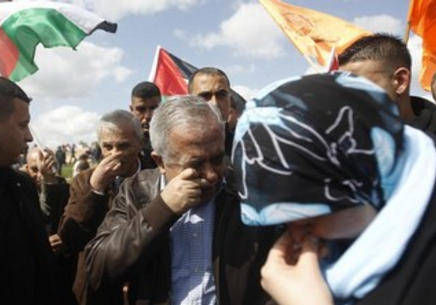 Palestinian Prime Minister Salam Fayyad (C) reacts from tear gas fired by IDF duriing Bilin protest