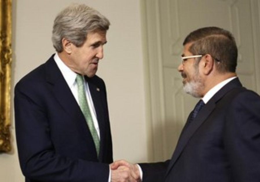US Secretary of State John Kerry (L) shakes hands with Egypt's President Mohamed Morsi in Cairo