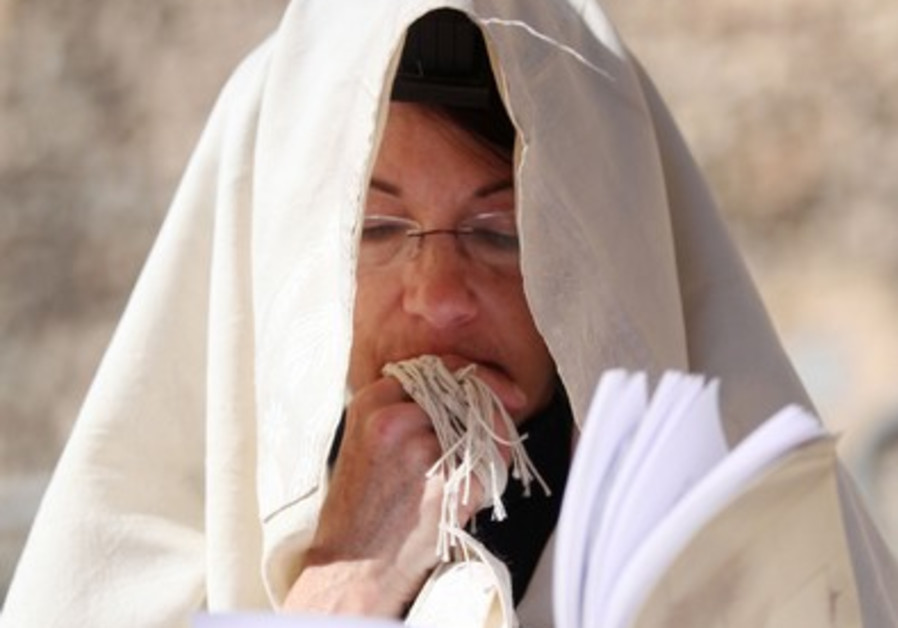A woman prays in a prayer shawl at the Western Wall