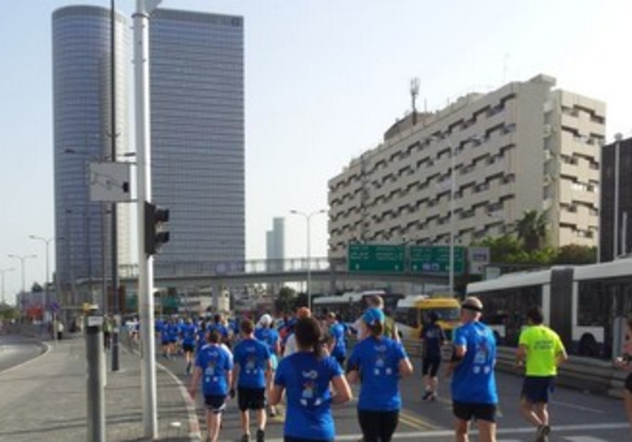 Tel Aviv marathon participants run down Menachem Begin road
