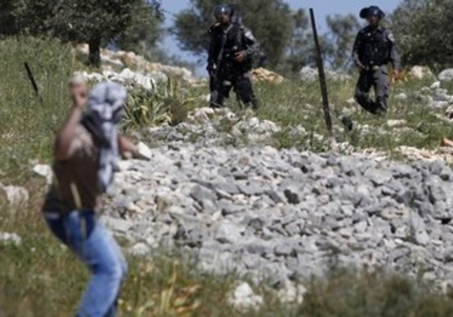 Palestinian throwing stones at Israeli border police near Nablus, March 29, 2013.