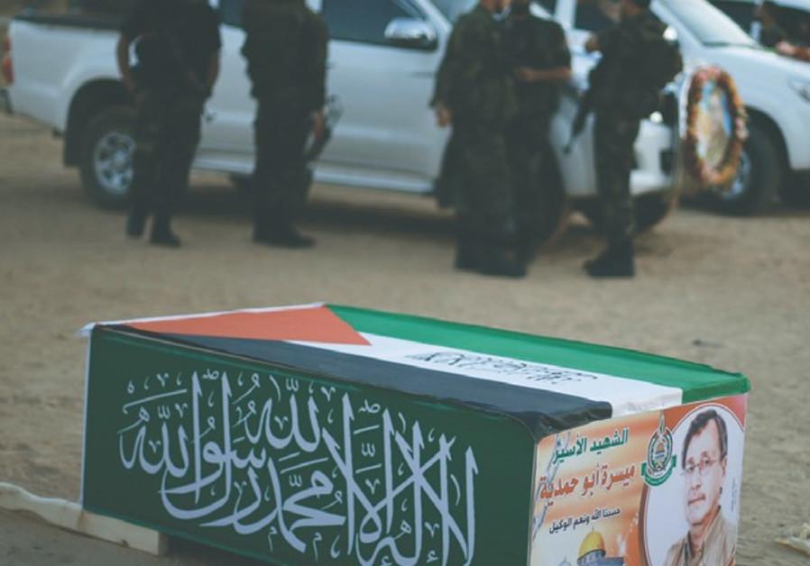 HAMAS MILITANTS stand near a mock coffin of Maissara Abu Hamdiyeh.
