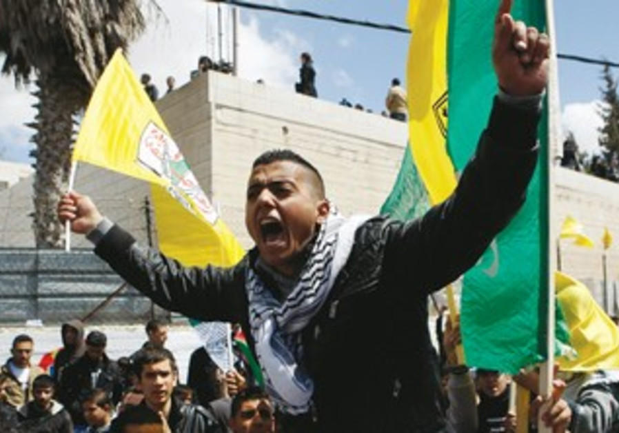 A Palestinian shouts as he holds a Fatah flag at the funeral of terrorist Maissara Abu Hamdiyeh.