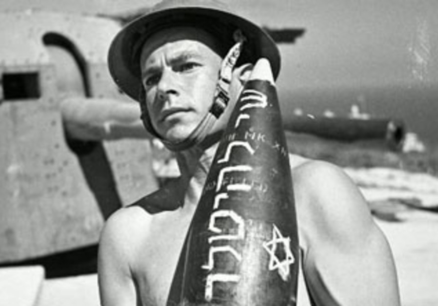 """A member of the British Army's WWII Jewish Brigade carries a rocket inscribed with """"gift for Hitler"""""""