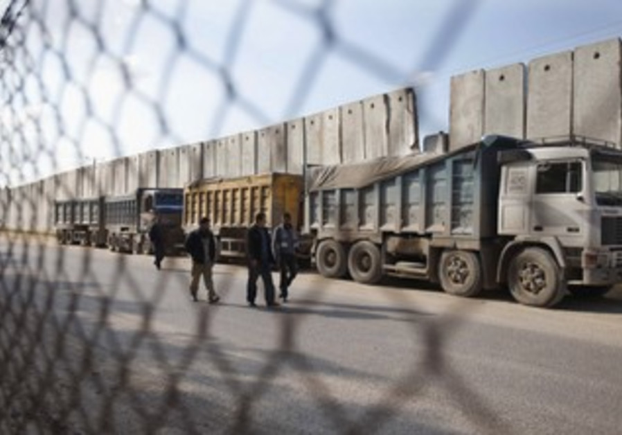 Palestinians walk past trucks loaded with gravel at the Kerem Shalom crossing December 30, 2012.