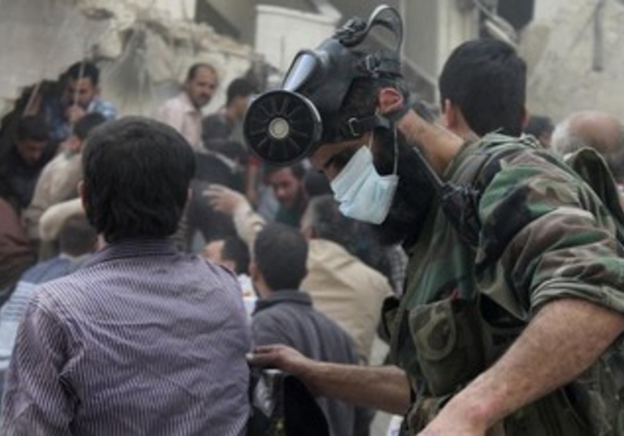 Man wearing a chemical mask searches for survivors in area hit by airstrike, Aleppo, April 11, 2013.