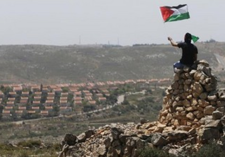 A Palestinian waves a flag in front of the W. Bank Jewish settlement of Ofra, April 26, 2013.