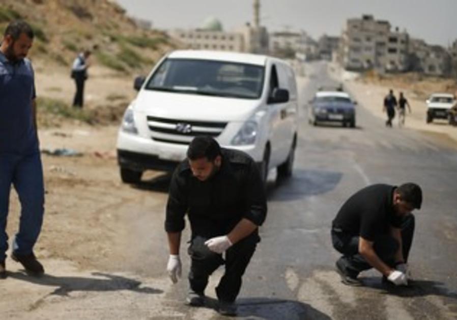 Palestinian police inspect scene after IAF strike in Gaza April 30, 2013