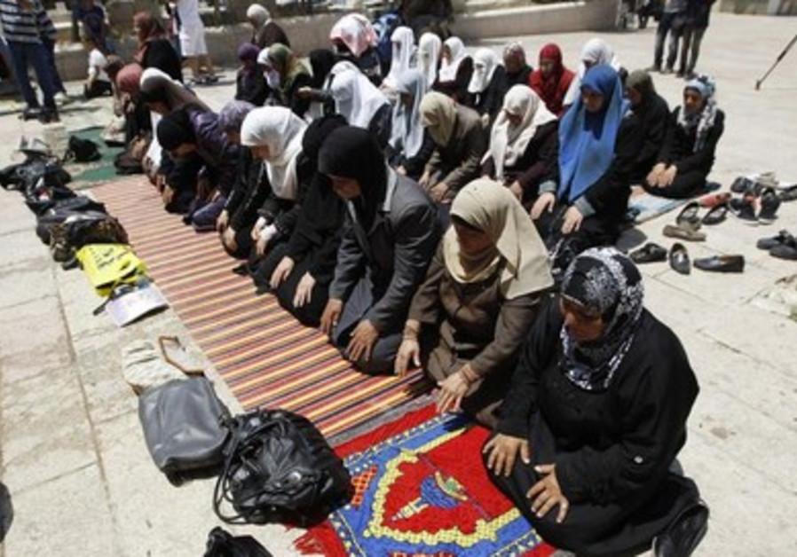 Palestinian women pray outside the Temple Mount following Jerusalem Day scuffles.