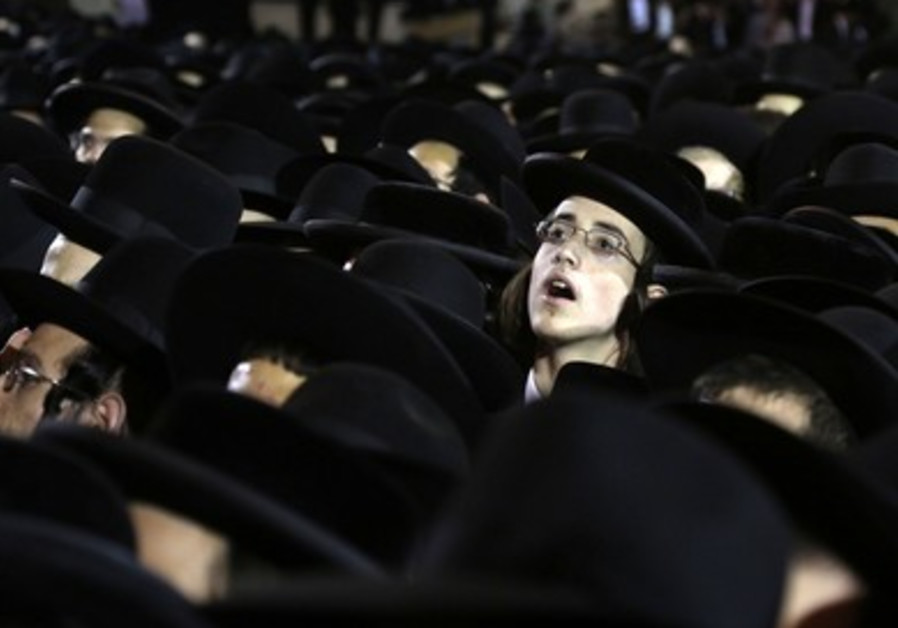Haredi boy peers out of crowd