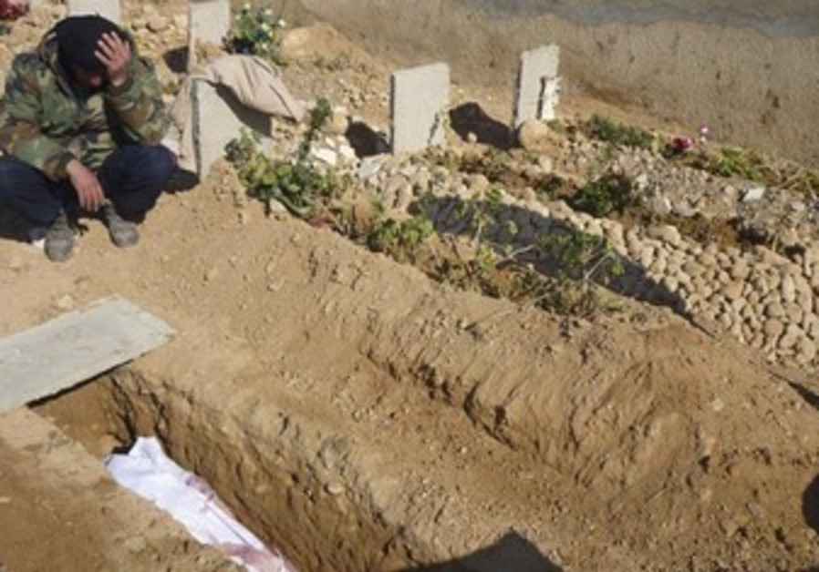 A Free Syrian Army fighter mourns near the grave of his comrade who died in clashes with Assad force