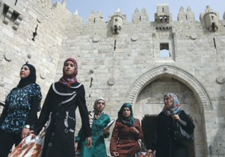 MUSLIM WOMEN walk outside of the Old City of Jerusalem's Damascus Gate