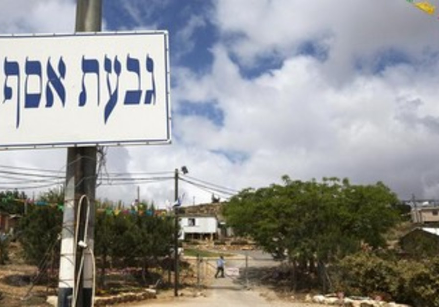 A sign post is seen at the entrance to the West Bank settler outpost of Givat Assaf near Ramallah.