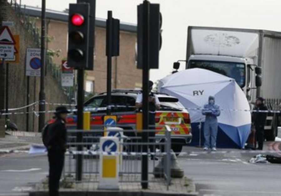A police forensics officer investigates a crime scene where one man was killed in Woolwich, London